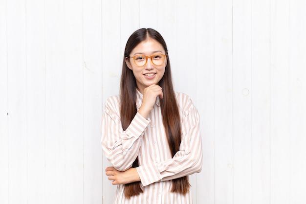 Giovane donna asiatica sorridente, godersi la vita, sentirsi felice, amichevole, soddisfatta e spensierata con la mano sul mento