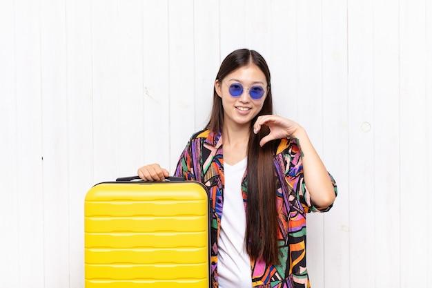 Giovane donna asiatica che sorride e si sente felice, carina, romantica e innamorata, facendo forma di cuore con entrambe le mani. concetto di vacanze