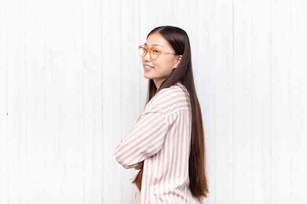 Giovane donna asiatica che sorride allegramente, sentendosi felice, soddisfatta e rilassata, con le braccia incrociate e guardando di lato