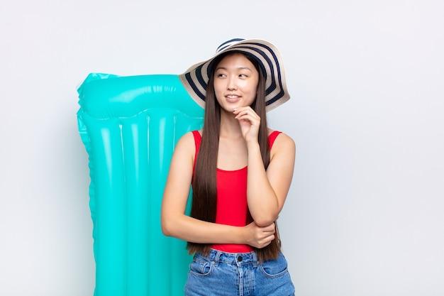 Giovane donna asiatica sorridente felicemente e fantasticando o dubitando, guardando al lato. concetto di estate