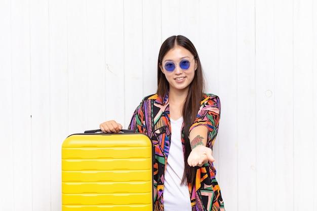 Giovane donna asiatica che sorride felicemente con sguardo amichevole, fiducioso, positivo, offrendo e mostrando un oggetto o un concetto.