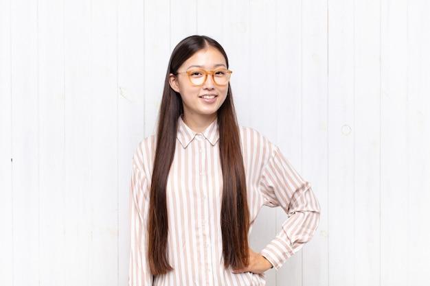 Giovane donna asiatica che sorride felicemente con una mano sull'anca e l'atteggiamento fiducioso, positivo, orgoglioso e amichevole