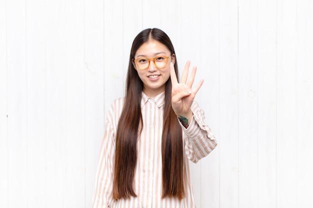Giovane donna asiatica che sorride e che sembra amichevole isolata