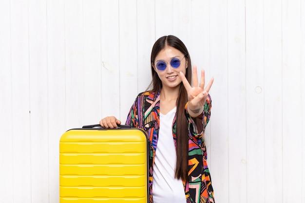 Giovane donna asiatica che sorride e che sembra amichevole, mostrando il numero quattro o quarto con la mano in avanti, contando alla rovescia. concetto di vacanze