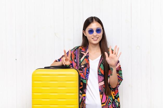 Giovane donna asiatica che sorride e che sembra amichevole, mostrando il numero sette o settimo con la mano in avanti, conto alla rovescia. concetto di vacanze