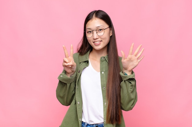 Giovane donna asiatica che sorride e sembra amichevole, mostrando il numero sette o settimo con la mano in avanti, conto alla rovescia