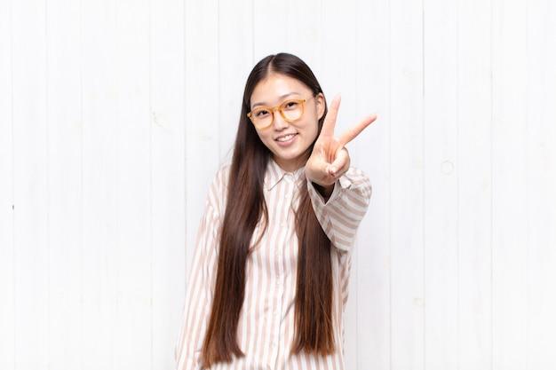 Giovane donna asiatica che sorride e che sembra felice, spensierata e positiva, gesticolando vittoria o pace con una mano