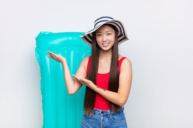 Giovane donna asiatica che sorride con orgoglio e sicurezza, sentendosi felice e soddisfatta e mostrando un concetto