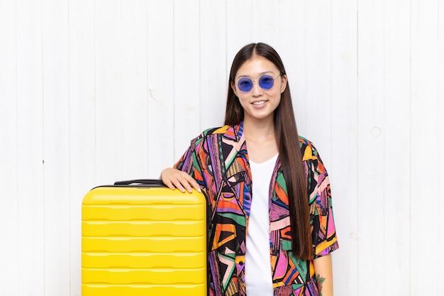 Giovane donna asiatica che sorride con le braccia incrociate e un'espressione felice, sicura, soddisfatta, vista laterale. concetto di vacanze