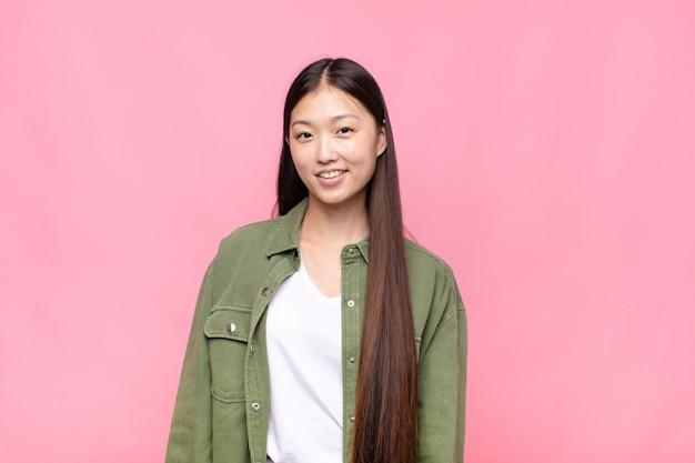 Giovane donna asiatica sorridente con le braccia incrociate e una felice espressione