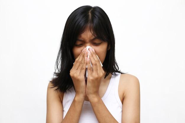 Giovane donna asiatica starnuti o tosse isolato su bianco