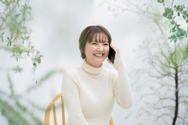 Giovane donna asiatica che parla su uno smartphone con il sorriso all'aperto