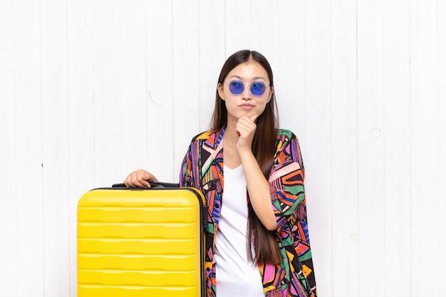 Giovane donna asiatica che pensa, che si sente dubbiosa e confusa, con diverse opzioni isolate