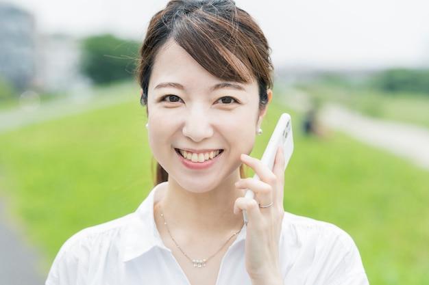 Giovane donna asiatica che per mezzo di uno smartphone