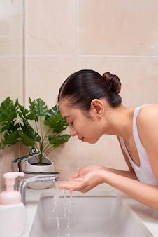 Giovane donna asiatica che si lava la faccia sul lavandino