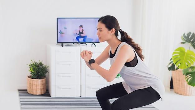 La giovane donna asiatica guarda l'allenamento video e si esercita a casa. concetto di esercizio durante la quarantena a casa per prevenire l'infezione da coronavirus e covid-19.