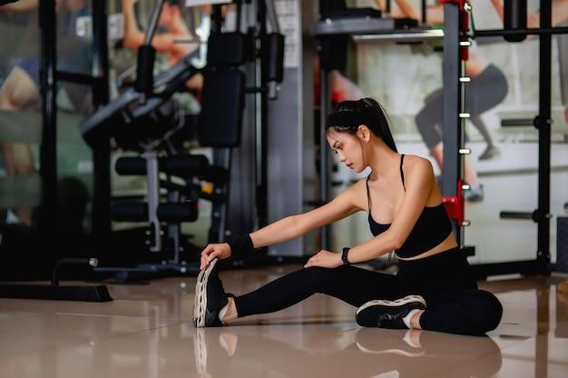 Giovane donna asiatica che indossa abbigliamento sportivo e smartwatch seduta sul pavimento e allunga i muscoli delle gambe e delle braccia prima dell'allenamento in palestra,