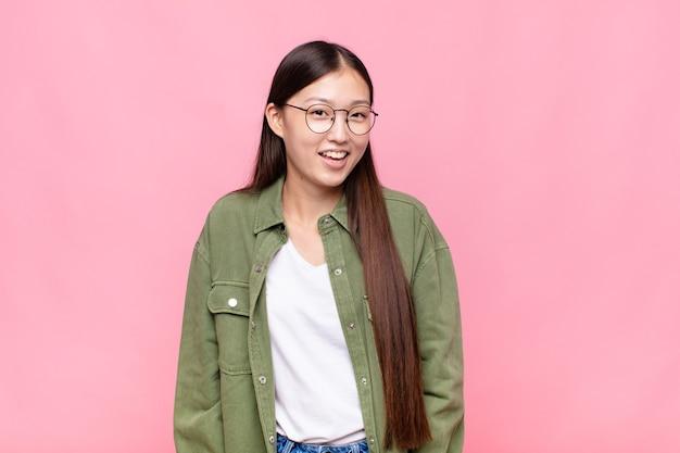 Giovane donna asiatica con un sorriso grande, amichevole e spensierato, che sembra positiva, rilassata e felice, agghiacciante