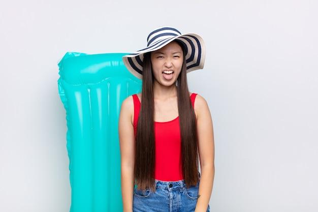 Giovane donna asiatica con un atteggiamento allegro, spensierato, ribelle, scherzando e tirando fuori la lingua, divertendosi. concetto di estate