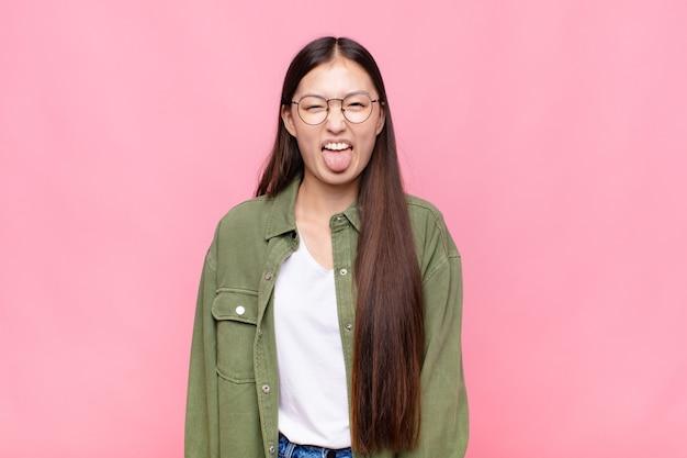 Giovane donna asiatica con atteggiamento allegro, spensierato, ribelle, scherzando e con la lingua fuori, divertendosi