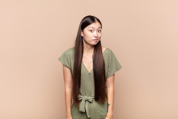 Giovane donna asiatica con un'espressione sciocca, pazza, sorpresa isolata