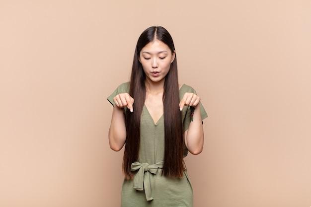 Giovane donna asiatica con la bocca aperta rivolta verso il basso con entrambe le mani