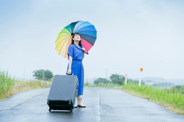 Giovane donna asiatica con valigia e ombrello colorato