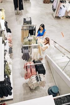 Giovani donne asiatiche che controllano i vestiti sugli scaffali nel grande magazzino, vista da sopra