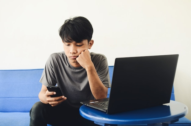 Giovani asiatici seduti sul divano davanti al laptop usando un telefono cellulare