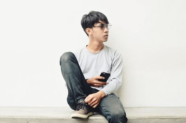 I giovani asiatici con gli occhiali sono seduti e portano un cellulare