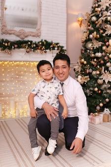 Papà e figlio asiatici ridono, sorridono e si abbracciano davanti al camino e all'albero di natale a casa