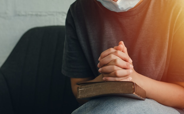 Richiesta di una crisi cristiana preghiera a dio una giovane donna che indossa una maschera prega dio per una vita migliore. mano femminile che prega dio con la bibbia chiedi perdono e fede nella bontà