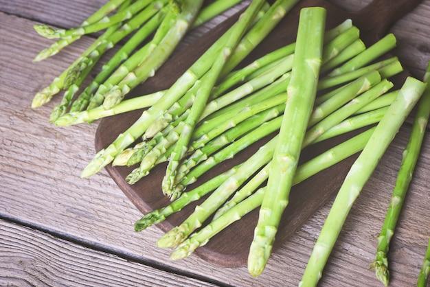 Mazzetto di asparagi per cibi cotti, fascio di asparagi verdi freschi su una tavola in legno rustico