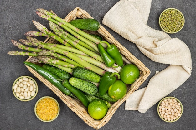 Asparagi, cetrioli e lime in cestino di rattan. mash, bulgur e noci in ciotole. tovagliolo beige. sfondo nero. lay piatto