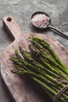Asparagi su un tagliere. cibo sano, salute su uno sfondo concreto.