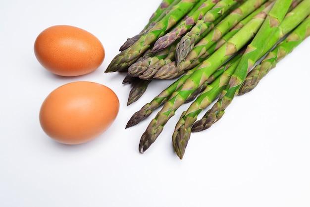 Asparagi e uova su uno sfondo bianco gruppo di asparagi crudi e uova su sfondo bianco come spazio di layout per il testo