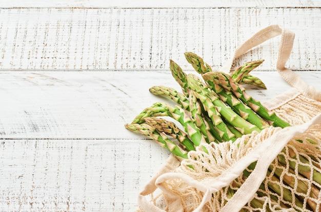 Asparago. mazzo di asparagi verdi freschi pronto per la cottura su fondo di legno vecchio bianco. spazio di copia vista dall'alto.