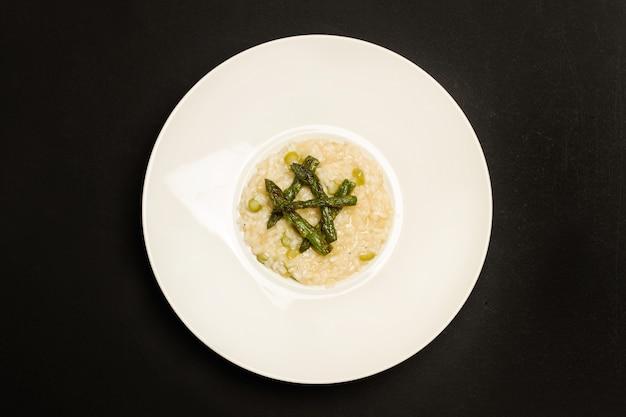 Risotto agli asparagi in un piatto di ceramica bianca in una vista dall'alto