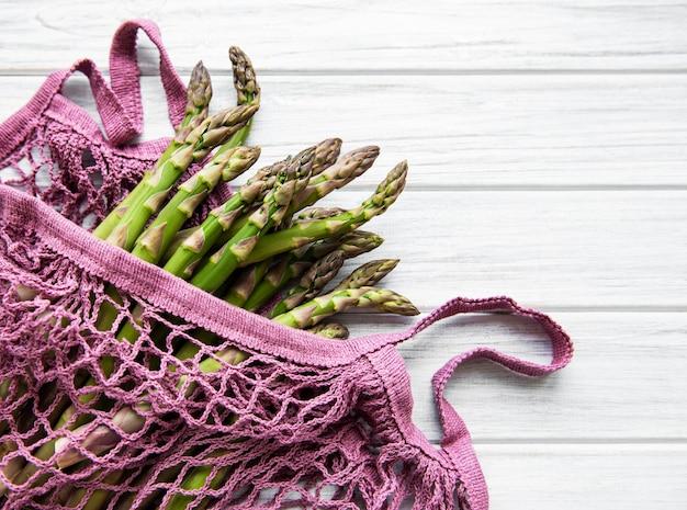 Gambi di asparagi in un sacchetto a rete ecologica su un vecchio fondo di legno