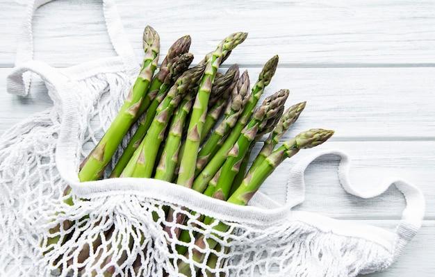 Gambi di asparagi in un sacchetto a rete ecologica su una vecchia superficie di legno