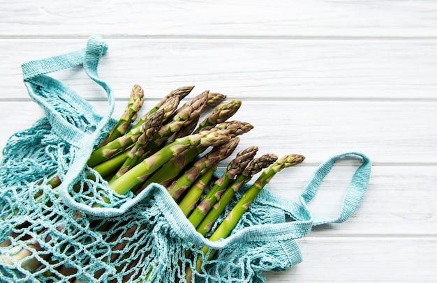 Gambi di asparagi in un sacchetto a rete ecologica su un vecchio tavolo di legno