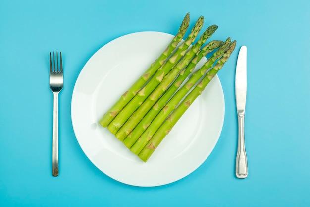 Asparagi su un piatto bianco su sfondo blu. asparagi vegetali freschi per una sana alimentazione e alimentazione.