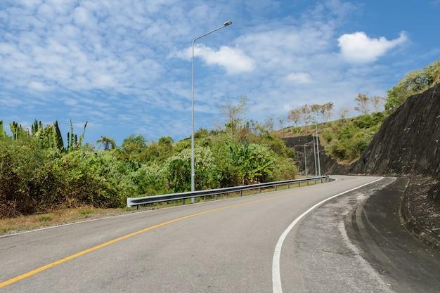 Strada curva asfaltata con palo di illuminazione in una giornata di sole