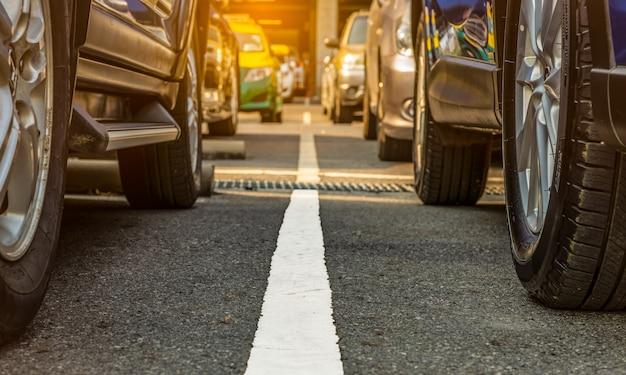Parcheggio asfaltato dell'aeroporto o del centro commerciale. posto auto in affitto. la ruota del primo piano di molte automobili ha parcheggiato al parcheggio fuori della porta. industria automobilistica.