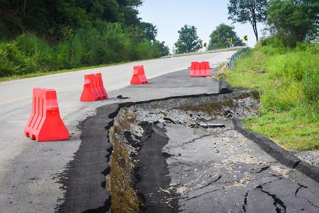 Strada asfaltata crollata e crepe sul ciglio della strada, frana stradale si abbassa con barriere di plastica in salita