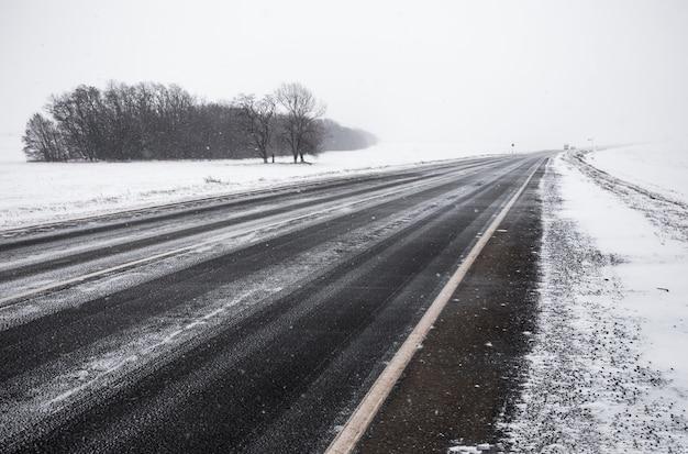Strada asfaltata che attraversa un campo nevoso.