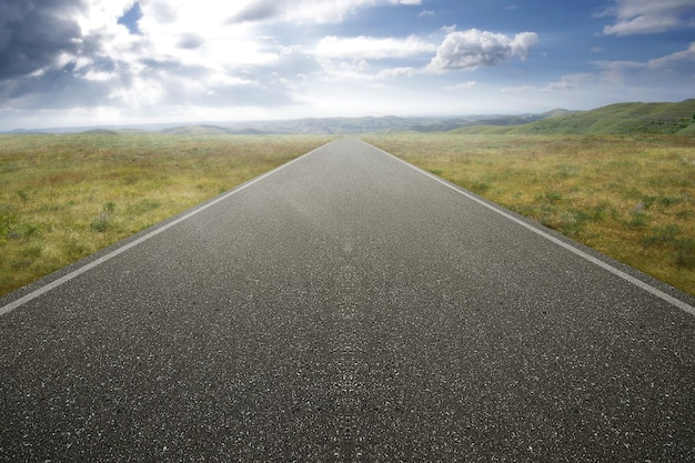 Strada asfaltata con erba verde e cielo blu