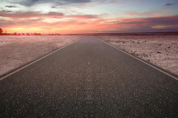 Strada asfaltata con albero e terra di siccità con uno sfondo di cielo al tramonto