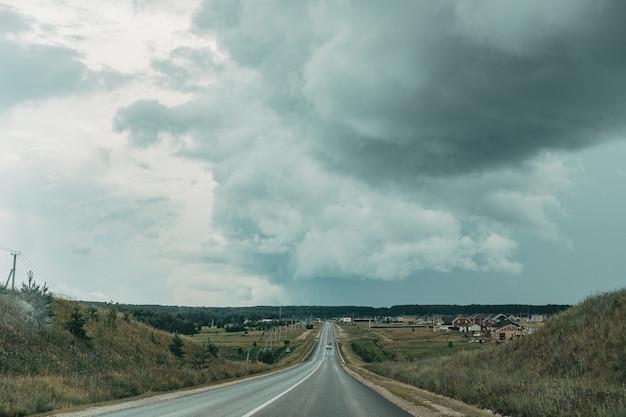 Strada asfaltata con uno sfondo tempestoso cielo scuro. pista vuota con nuvole nere