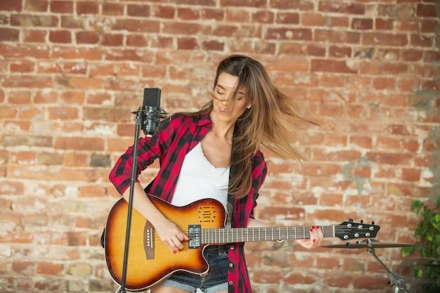 Aspirazione. bella donna in cuffia che registra musica, canta e suona la chitarra mentre è seduta in un loft sul posto di lavoro oa casa. concetto di hobby, musica, arte e creazione. creazione del primo singolo.